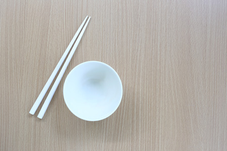 housewares: White chopsticks and dish in top view on wood background for design concept food.