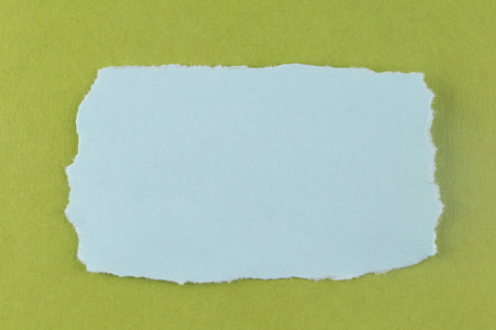 input: Blue paper tear on green cardboard background and you can input text in copy space. Stock Photo