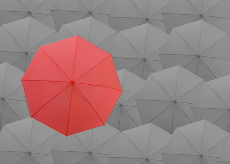 best security: Red umbrella on the top of gray umbrellas background in concept of business competition and leader concept in being different.