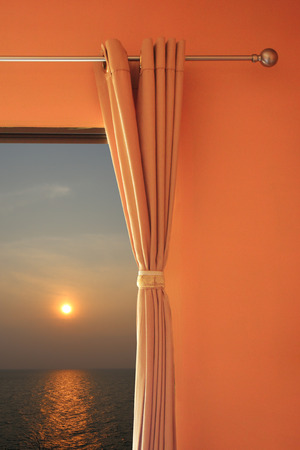 visible: bedroom windows open and visible sunset at sea to concept of relaxing holiday.