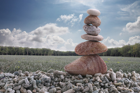 rock pile: Balance stone on pile rock with agricultural area background for concept of Zen and calm.