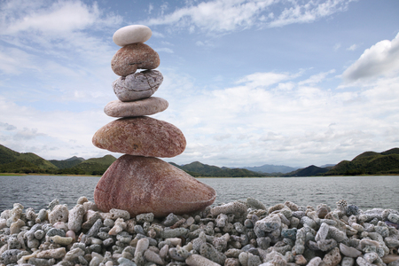 rock pile: Balance stone on pile rock with river background for concept of Zen and calm. Stock Photo