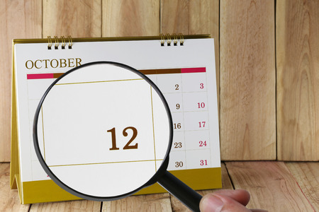 scheduling system: Magnifying glass in hand on calendar you can look Twelfth date of month,Focus number twelve in October,Concept in business and meetings.