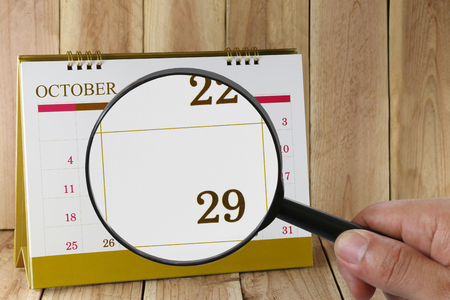 scheduling system: Magnifying glass in hand on calendar you can look Twenty-nine date of month,Focus number Twenty-nine in October,Concept in business and meetings. Stock Photo