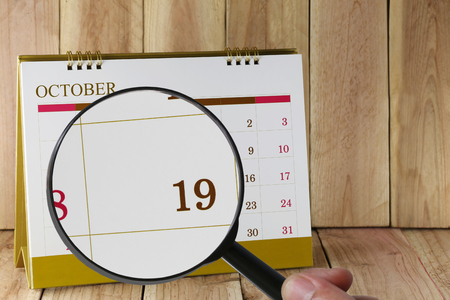 nineteen: Magnifying glass in hand on calendar you can look Nineteenth date of month,Focus number nineteen in October,Concept in business and meetings. Stock Photo