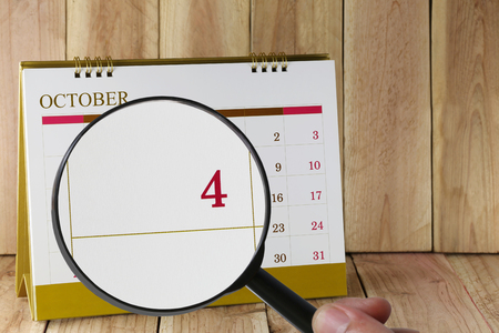 scheduling system: Magnifying glass in hand on calendar you can look Fourth date of month,Focus number four in October,Concept in business and meetings. Stock Photo