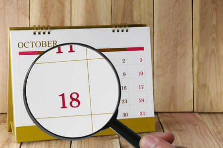 eighteen: Magnifying glass in hand on calendar you can look Eighteenth date of month,Focus number Eighteen in October,Concept in business and meetings. Stock Photo