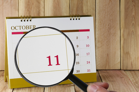 scheduling system: Magnifying glass in hand on calendar you can look Eleventh date of month,Focus number eleven in October,Concept in business and meetings. Stock Photo