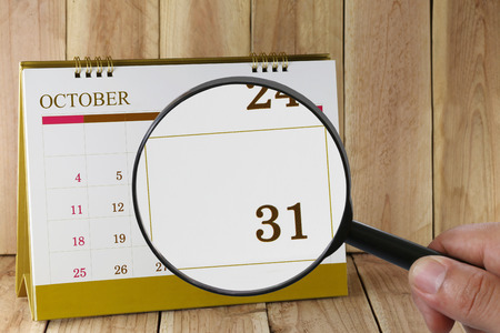 Magnifying glass in hand on calendar you can look thirty-one date of month,Focus number thirty one in October,Concept in business and meetings. Stock Photo