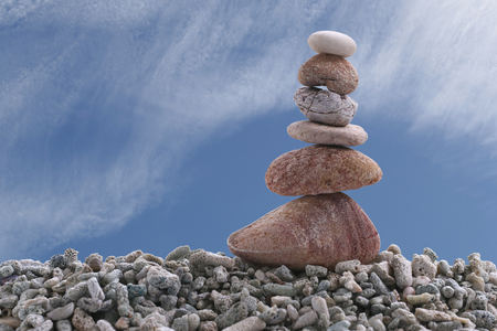 Balance stone on pile rock with blue sky background for concept of Zen and calm.