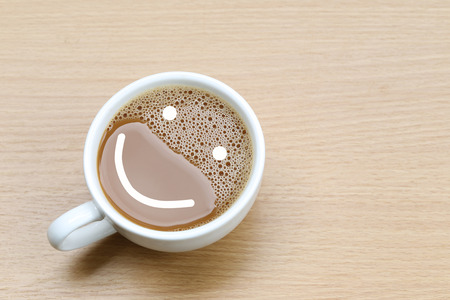frothy: hot coffee in a white Coffee cup on wooden table at coffee shop and Symbol of smile.