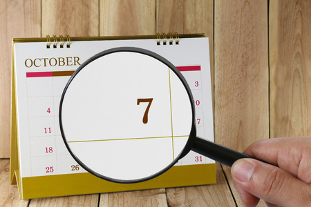 Magnifying glass in hand on calendar you can look seventh date of month,Focus number seven in October,Concept in business and meetings.
