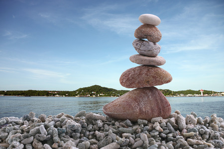 Balance stone on pile rock with sea background for concept of Zen and calm.