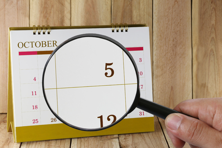 Magnifying glass in hand on calendar you can look fifth date of month,Focus number five in October,Concept in business and meetings.