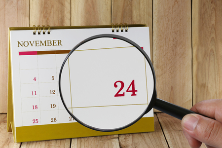 scheduling system: Magnifying glass in hand on calendar you can look Twenty-four days of month,Focus number Twenty-four in November,Concept in business and meetings. Stock Photo