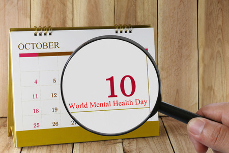 relaciones p�blicas: Magnifying glass in hand on calendar you can look World Mental Health Day in 10 October,concept of a public relations campaign Mental health and stress. Foto de archivo