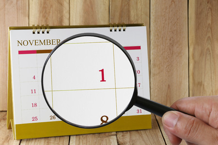 scheduling system: Magnifying glass in hand on calendar you can look first day of month,Focus number one in November,Concept in business and meetings. Stock Photo