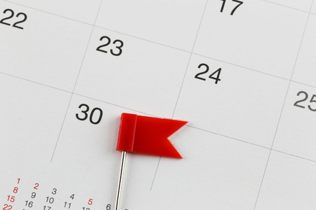 Red Pins to Placed on the calendar beside the number of thirty in business concept time and date. Stock Photo