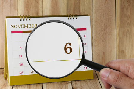 scheduling system: Magnifying glass in hand on calendar you can look Sixth day of month,Focus number one in November,Concept in business and meetings.
