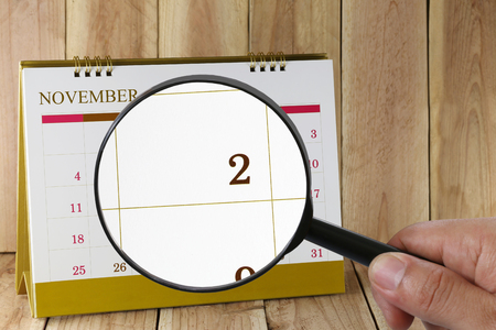scheduling system: Magnifying glass in hand on calendar you can look second day of month,Focus number two in November,Concept in business and meetings.