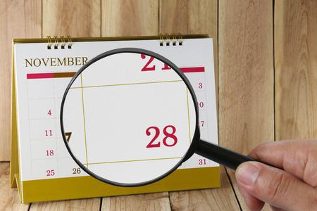 scheduling system: Magnifying glass in hand on calendar you can look Twenty-eight day of month,Focus number Twenty-eight in November,Concept in business and meetings.
