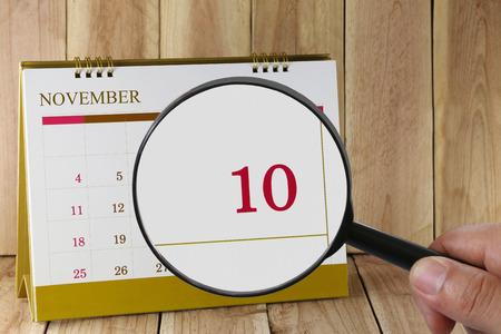 numero diez: Lupa a disposición en el calendario se puede mirar décimo día del mes, se centran en el número diez de noviembre de concepto en los negocios y reuniones. Foto de archivo