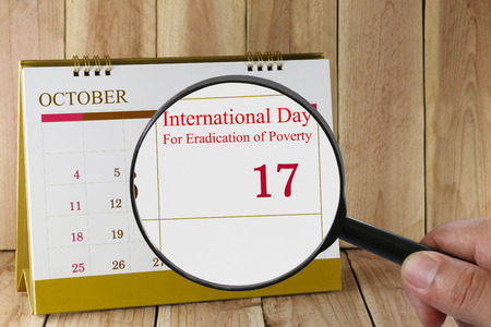 eradication: Magnifying glass in hand on calendar you can look International Day For Eradication of Poverty on 17 October,concept of a public relations campaign economy and society.