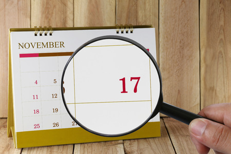 scheduling system: Magnifying glass in hand on calendar you can look seventeenth day of month,Focus number seventeen in November,Concept in business and meetings.