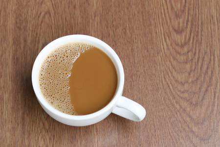 frothy: hot coffee in a white Coffee cup on wooden table at coffee shop. Stock Photo
