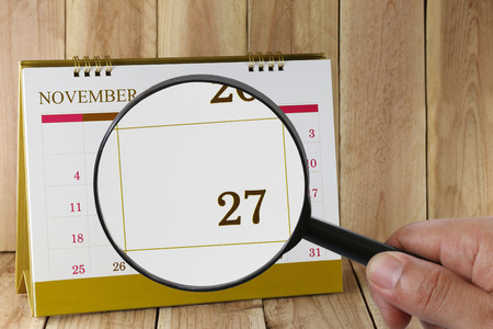 scheduling system: Magnifying glass in hand on calendar you can look Twenty seven day of month,Focus number Twenty seven in November,Concept in business and meetings.