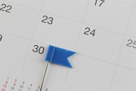 Blue Pins to Placed on the calendar beside the number of thirty in business concept time and date. Stock Photo