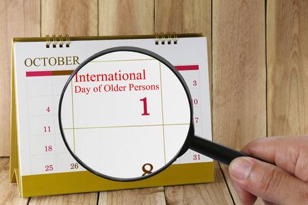 relaciones publicas: Lupa a disposición en el calendario se puede mirar el Día Internacional de las Personas de Edad, con fecha 01 de octubre de concepto de una campaña de relaciones públicas.