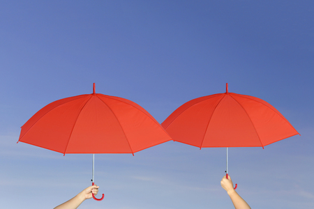 sun protection: Red umbrella in hand on blue sky background concept of sun protection.