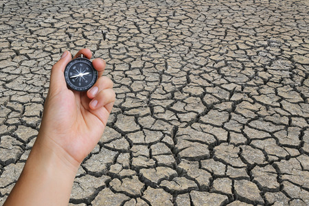 barrenness: hand of a man holding a compass and cracked land in the countryside,concept of journey and aridity. Stock Photo