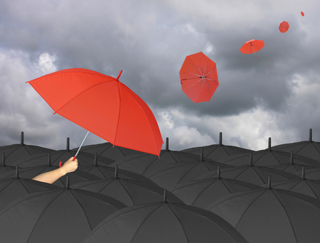 blown: Red umbrella in hand and Surrounded by a black umbrella,umbrella other blown by wind,concept for management business idea on rain cloud background.