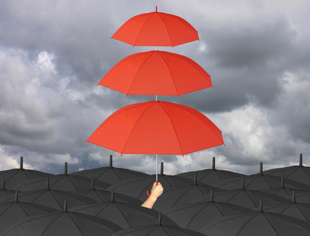 wind blown: Red umbrella third layers in hand and rain protection more than black umbrella,concept for management business idea on rain cloud background.