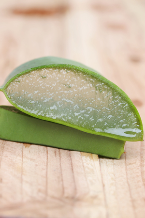 neutralize: aloe vera slice on wooden floor and can you see texture of aloe vera gel.