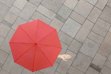 protruding: Red umbrella and a hand of man standing on stone floor and hand protruding outside the radius to determine whether it rains or not,concept of risks in business.