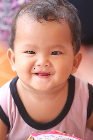 the innocence: Asian baby eating a dragon fruit with happily,concept of health and foods of the children.