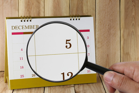 scheduling system: Magnifying glass in hand on calendar you can look fifth date of month,Focus number five in December,Concept in business and meetings.