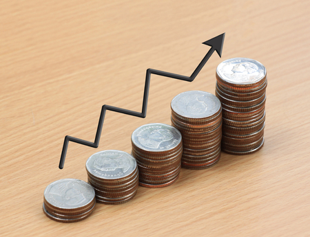 silver coin stack and arrow line in business growth concept on wood floor.