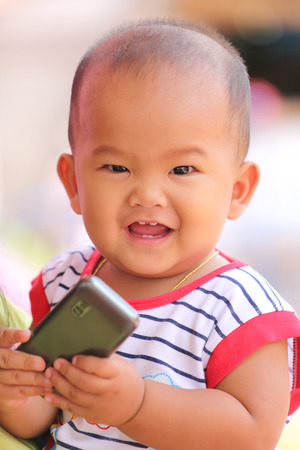 teething: Asian baby in hand hold a mobile and smile with happily,concept of health and development of the children. Stock Photo