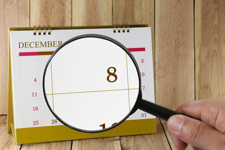 scheduling system: Magnifying glass in hand on calendar you can look eighth date of month,Focus number eight in December,Concept in business and meetings.