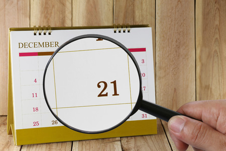 scheduling system: Magnifying glass in hand on calendar you can look Twenty-one date of month,Focus number Twenty-one in December,Concept in business and meetings.