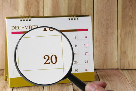 twentieth: Magnifying glass in hand on calendar you can look twentieth date of month,Focus number twenty in December,Concept in business and meetings.