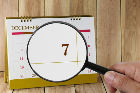 scheduling system: Magnifying glass in hand on calendar you can look seventh date of month,Focus number seven in December,Concept in business and meetings. Stock Photo