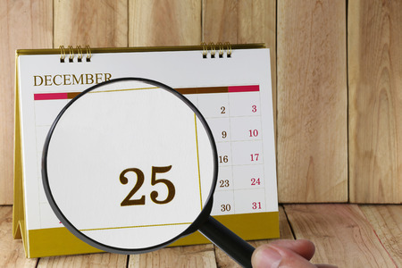 twenty five: Magnifying glass in hand on calendar you can look Twenty Five date of month,Focus number Twenty Five in December,Concept in business and meetings.