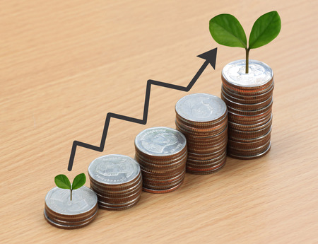 silver coin stack and arrow line and have treetop in business growth concept on wood floor. Stock Photo