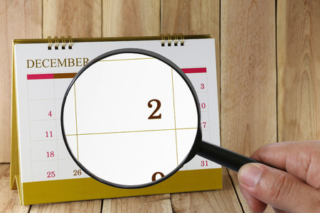 scheduling system: Magnifying glass in hand on calendar you can look two date of month,Focus number two in December,Concept in business and meetings.