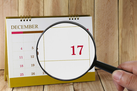 seventeenth: Magnifying glass in hand on calendar you can look Seventeenth date of month,Focus number seventeen in December,Concept in business and meetings. Stock Photo